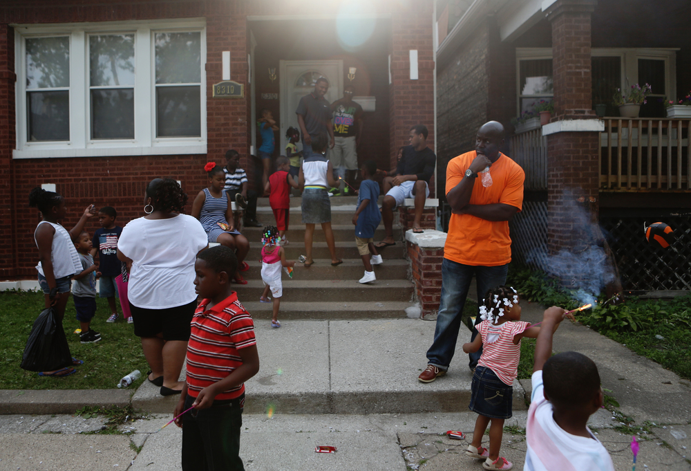 Daniel Taylor, center, watches his nieces and nephews play in front of his Aunt Marie's house on Thursday, July 4, 2013.  Nearly all of his nieces and nephews were born while he was incarcerated.  The Fourth of July was the first time that he met many of them and he said that the experience was overwhelming.