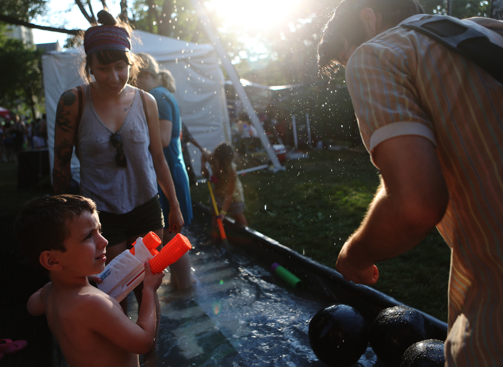 "Oliver Dennison, 5, aims his water gun at Steven McDonough at the Pitchfork Music Festival in Chicago's Union Park on Saturday, July 20, 2013.  Oliver was hesitant, because he said, ""My parents told me not to spray people in the face."""