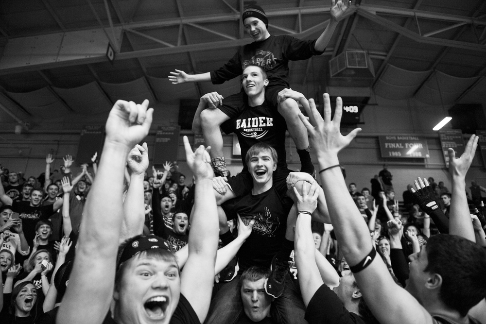 Southridge senior Ethan Schwoeppe, bottom, Luke Stetter, junior, Drew Dearing, freshman, and Braden Harding, freshman, stacked on top of each other and cheered with the rest of the student section during halftime of their game against Washington in the IHSAA Class 3A sectional tournament in Huntingburg on Wednesday.  The Raiders lost 41-35.