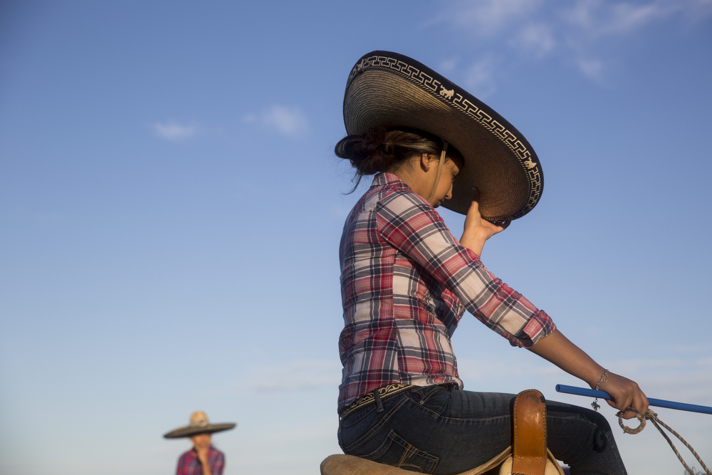Brenda Murillo adjusts her sombrero before the team practiced their routine in the pre-state arena at El Rancho Unico in Atascosa, Texas on March 26, 2015.  Emely Ayala, a teammate, fell off the weekend before pre-state and was too scared to compete.  Murillo filled her spot so that the team could compete.