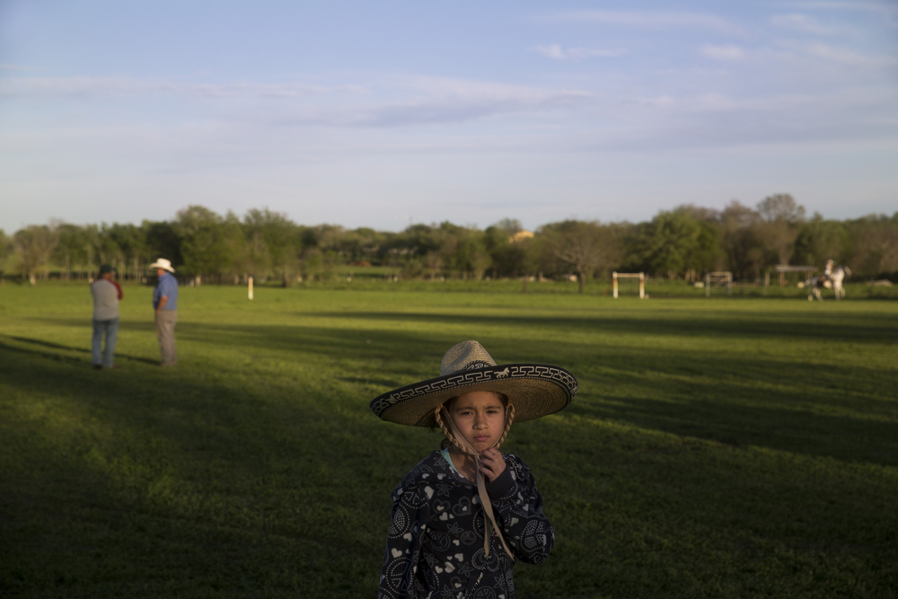 "Emely Ayala adjusts her sombrero while watching her teammates practice for pre-state at El Rancho Unico in Atascosa, Texas on March 26, 2015.  After falling off during practice that Sunday, she became too scared to ride with the team.  Jimmy Ayala, her father and the team's coach, did not want to push her to ride if she was not ready, so she stood by watching and helping her team from the ground.  ""When she told me she was scared, I wanted her to be 100 percent before riding again,"" Ayala said.  ""I wasn't going to risk not only my daughter, but also the team.  If her nerves took over, someone else could have gotten hurt."""