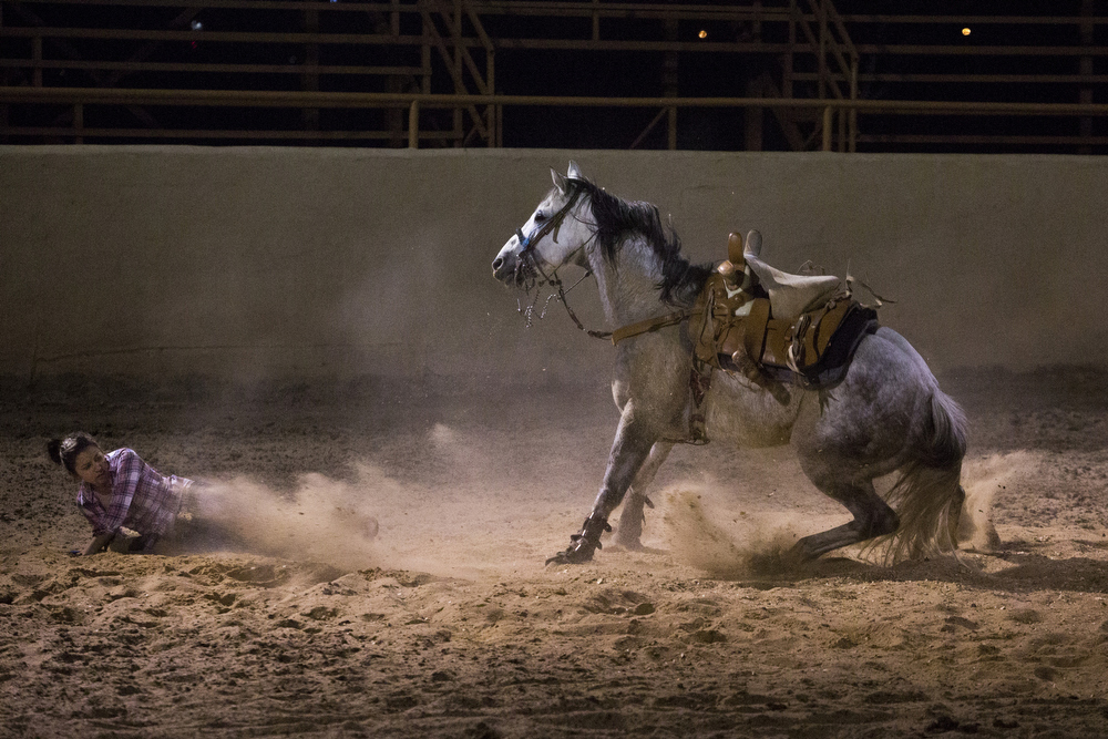 "Brenda Murillo hits the ground after she and her horse Cazador slipped and fell during a ""punta,"" or slide stop, at Rancho San Miguel in Atascosa, Texas on March 26, 2015.  This was Murillo's first time falling off, she said.  Despite that, she got back on moments later and tried to do a punta again, this time with success.  ""When an escaramuza falls, they just dust off their dress and get right back on,"" Coach Jimmy Ayala said."