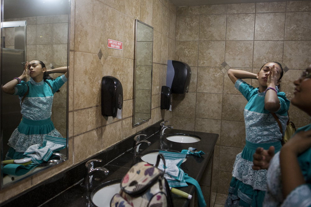 Jackie Ayala and Kristy Escamilla do their hair in the bathroom of a gas station along I-35 on February 21, 2015.  The girls were on their way to represent the team at Junta Estatal para Capitanas, or the State Meeting for Captains, in Temple, Texas.