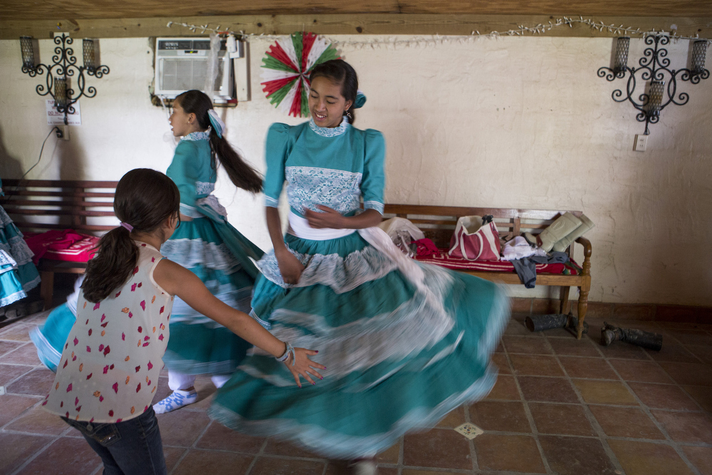 "Emely Ayala, left, watches as her older sister Jackie Ayala spins in her escaramuza dress before performing in the ""A Day in Old Mexico"" Charreada at the San Antonio Charros Association in San Antonio, Texas on April 26, 2015. Each dress must be handmade with specific guidelines to maintain the cultural traditions of the sport as it has been for generations in Mexico.  ""I am following in my great grandfather's footsteps"" Jackie Ayala said.  ""He was a charro in Coahuila, Mexico, so I want to continue the tradition."""