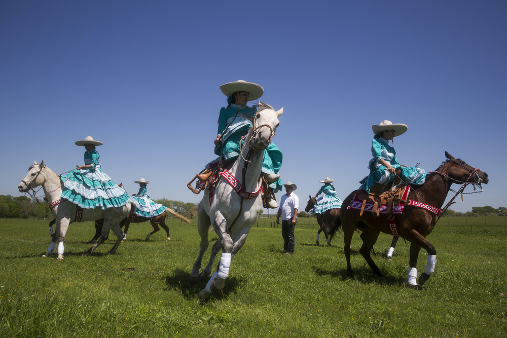 "Escaramuza Las Potrancas warm up for their pre-state performance at El Rancho Unico in Atascosa, Texas on March 29, 2015.  ""I believe in y'all,"" Emely Ayala, 8, said to her team after warm-ups. ""Whatever happens, just keep on going."""