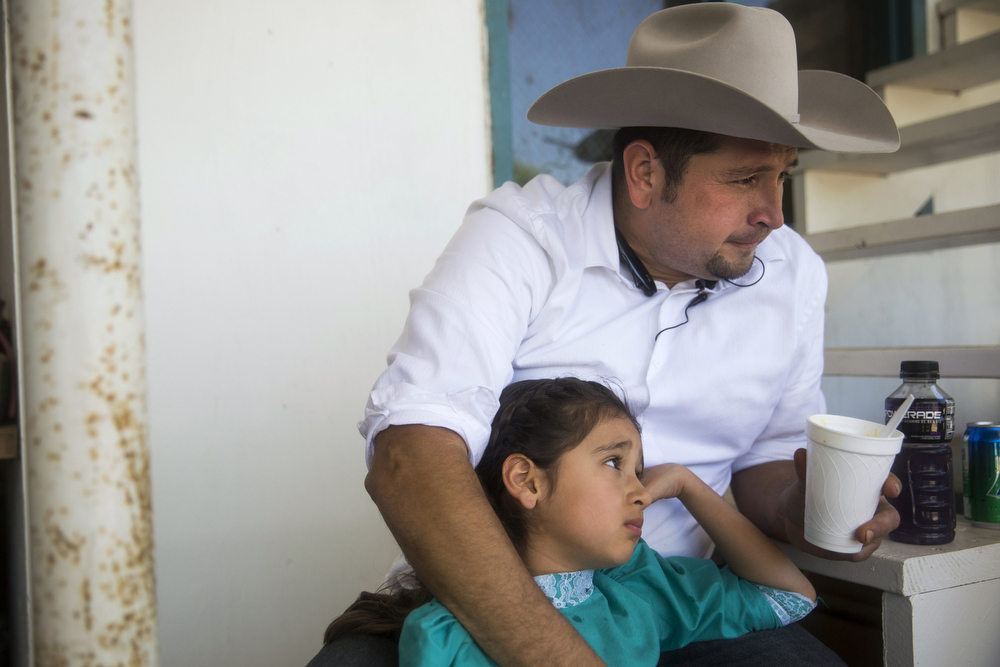 "Emely Ayala rests in the shade with her father Jimmy Ayala while waiting to perform in Pre-Estatal at El Rancho Unico in Atascosa, Texas on March 29, 2015.  ""It is hard to protect them in such a dangerous sport, but what takes away from the danger is hard work in practice,"" Ayala said. ""This sport helped them get through when I got divorced from their mom nine years ago.  It is what kept us so close."""