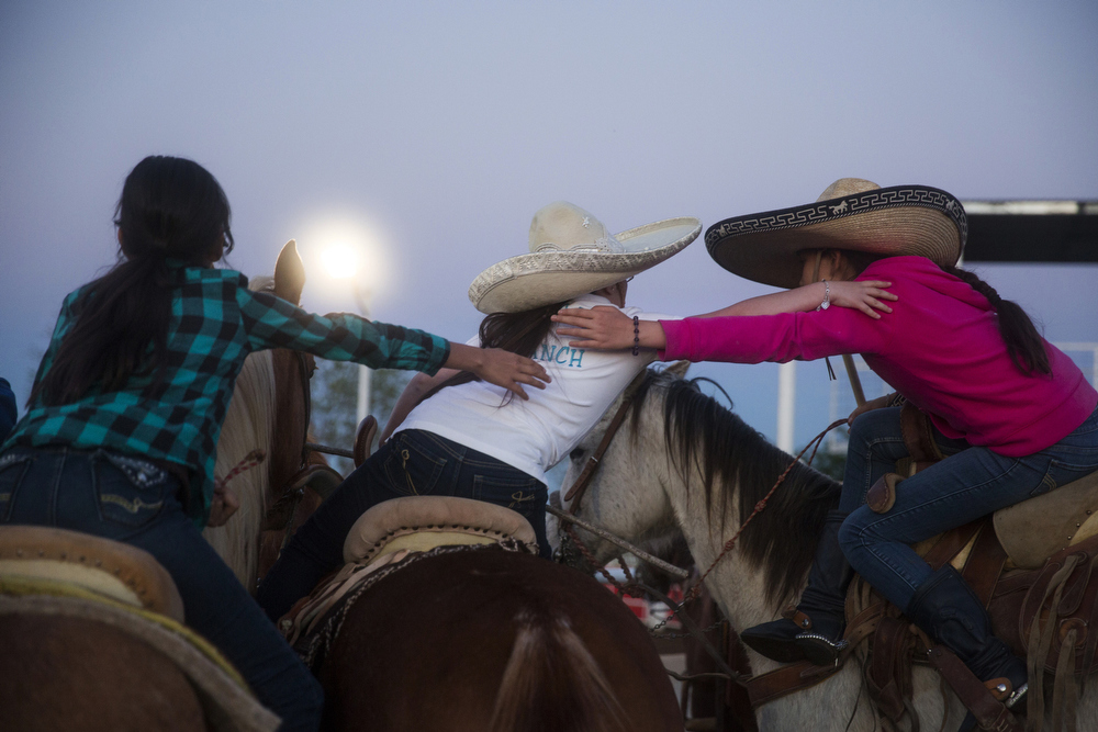 Miriam Alejandra Montecillos, Yaretzi Peña and Andrea Murillo lean over for a group hug after practice at El Rancho Unico in Atascosa, Texas on March 26, 2015.  Peña is from another team, Escaramuza Orgullo Mexicano.  She used to be a part of Murillo and Montecillos' team and the girls remain friends.