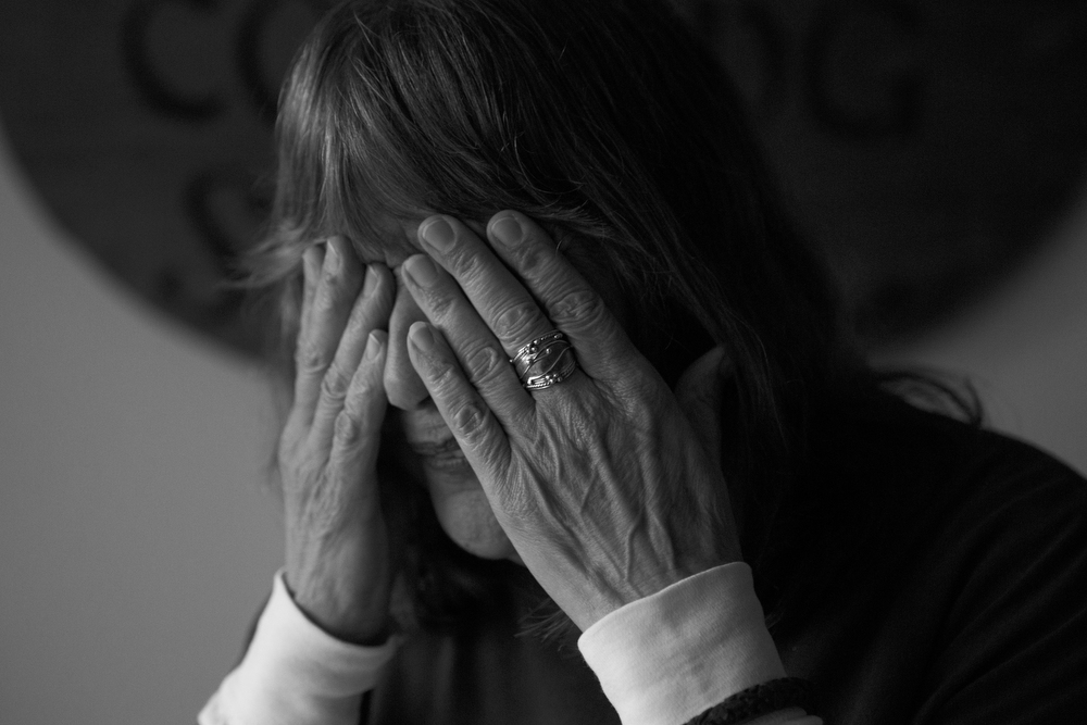 "Marti Sousanis puts her hands over her face as she tells a story in her home in San Francisco, Calif. on June 2, 2015.  Eight years ago, Sousanis was evicted through the Ellis Act, which is a state law giving landlords the right to evict all of the tenants in a building in order to shut down their business, often with the intention of selling the building for a profit.  After getting pushed out of the Mission neighborhood years ago, she now faces eviction for a second time.  Her rent has increased by $650 since January.  Before the increase, Sousanis, who has lived in the city for over fifty years, said she was already living solely on her social security checks.  ""Since the increase, I have maxed out two credit cards and am working on a third just paying for food and doctors,"" she said.  ""I don't qualify for food stamps, because my rent is too high.  The irony! ...I had to go to a charity to ask for money for the first time in my life, just so I could avoid eviction for a little while longer.  I am a part of what has made this city the creative, tolerant city that it is.  You are taking me away from my home, my friends, my business, my everything."""