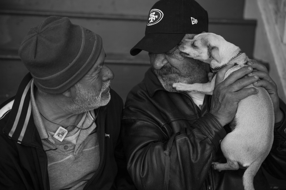 "Daniel Dupont watches as Roberto Solarzano gets a kiss from Dupont's dog Mandy while they sit on the stoop of the house Dupont used to live in with his wife in the Mission neighborhood of San Francisco, Calif. on June 3, 2015.  Dupont and Solarzano are currently homeless.  Dupont's wife died two months ago, leaving him to care for her dog, Mandy.  Dupont said he loves Mandy as a way to keep loving his wife.  Solarzano has lived in the Mission for 44 years.  ""Even if you have a job, it doesn't mean you can afford to live here,"" he said."