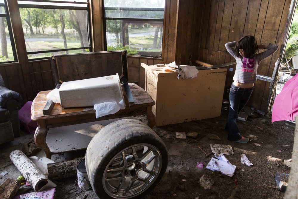 "Serenity Bamberger, 7, looks at the damage in her home in Blanco, Texas on Friday, May 29, 2015. Of the donations that have flooded in to help Serenity and her family, she said, ""It is like Christmas.""  However, her mother Glenda Bamberger said that Serenity and her sister Cielo were very upset at first."