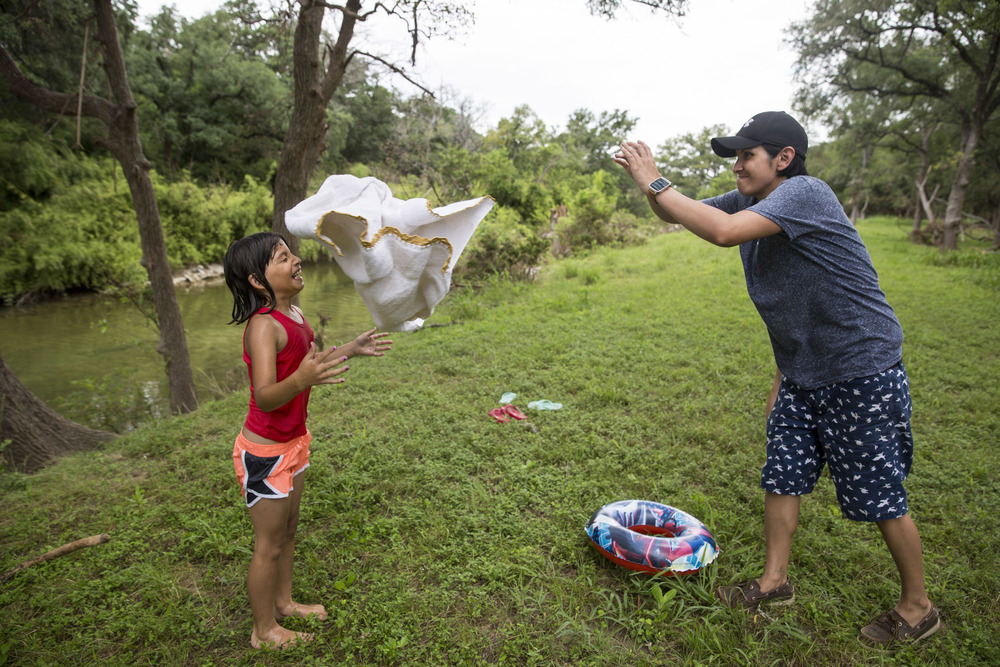 Glenda Bamberger, right, tosses a towel at Serenity Bamberger, 7, after Serenity finished swimming in the Little Blanco River behind their home in Blanco, Texas on July 1, 2015.  A month and a half prior, the same river flooded their home destroying the majority of the family's belongings.