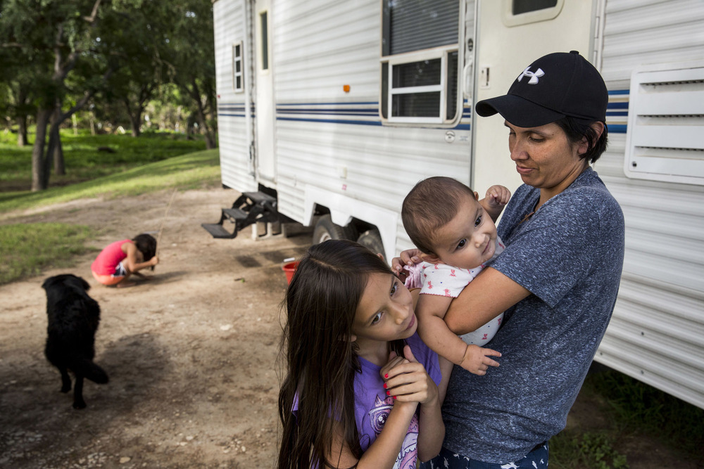 Cielo Bamberger, 10, and Esmebella Bamberger, 9 months, hang on their mother Glenda Bamberger while their sister Serenity Bamberger, 7, digs in the dirt outside of their RV on their property in Blanco, Texas on July 1, 2015.  The family is living in the RV, which is parked in front of their flood-damaged home, while they build a new house on eight-foot pillars on the same property.  The dog, known as Buddy or Bear, showed up on their property after the floods and has stayed since.   Glenda said that she thinks he was carried far from his home in the floods, because none of their neighbors in the area have claimed him.
