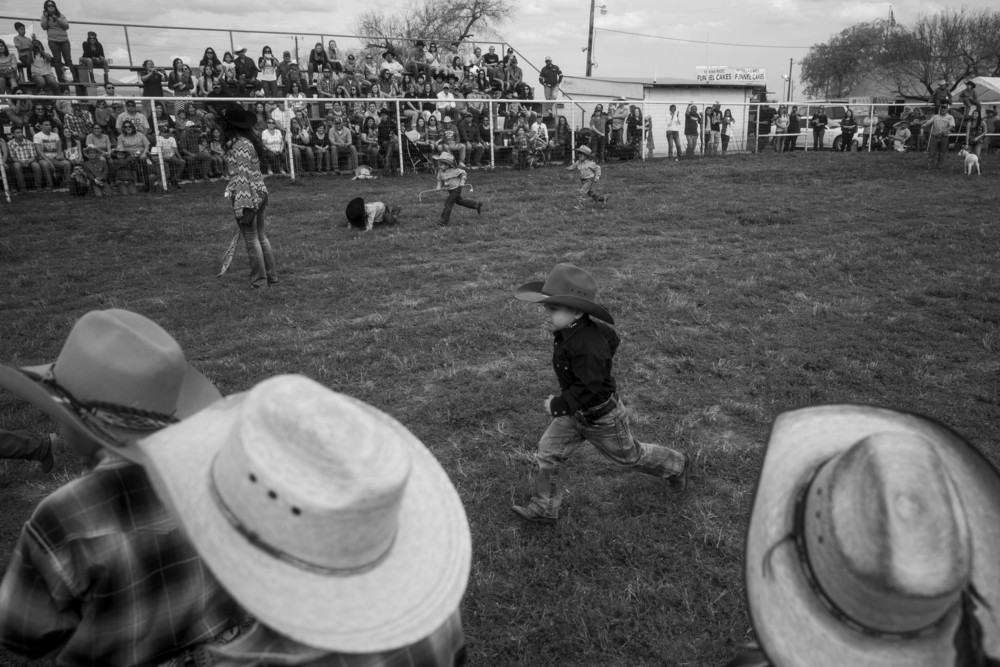 The Cotulla Vaqueros watch as Breyon Deltoro, 4, of the Little Vaqueros, races back to the finish line during the goat tagging relay for children six years and under at the LaSalle County Fair and Wild Hog Cookoff in Cotulla, Texas on March 13, 2015.  Their fathers all worked in the oil fields.
