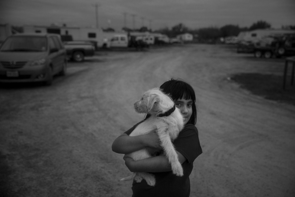 Bianca Chaires, 8, holds her family's puppy Brisket as she walks down the road that winds through the Cotulla RV Park in Cotulla, Texas on March 7, 2015.  The RV park serves the oil field workers and their companies who want to have a more affordable and home-like living arrangement.  She lives in one of the trailers with her family.