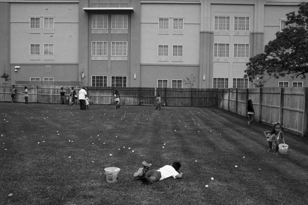 "The LaQuinta Inn and Suites looms over the backyard as children go on an Easter egg hunt at Jessie Galindo's house in Cotulla, Texas on April 5, 2015.  Her husband, father, uncle and other members of her family all work in the oil field.  ""Jessie hates having the hotels around her house because now any random stranger can watch her and her kids play in the yard.  There is no privacy in this town anymore,"" Galindo's sister JoAnna Gonzalez said.  Towns like Cotulla that experienced great growth in the oil boom did not have zoning policies in place to deal with that growth."