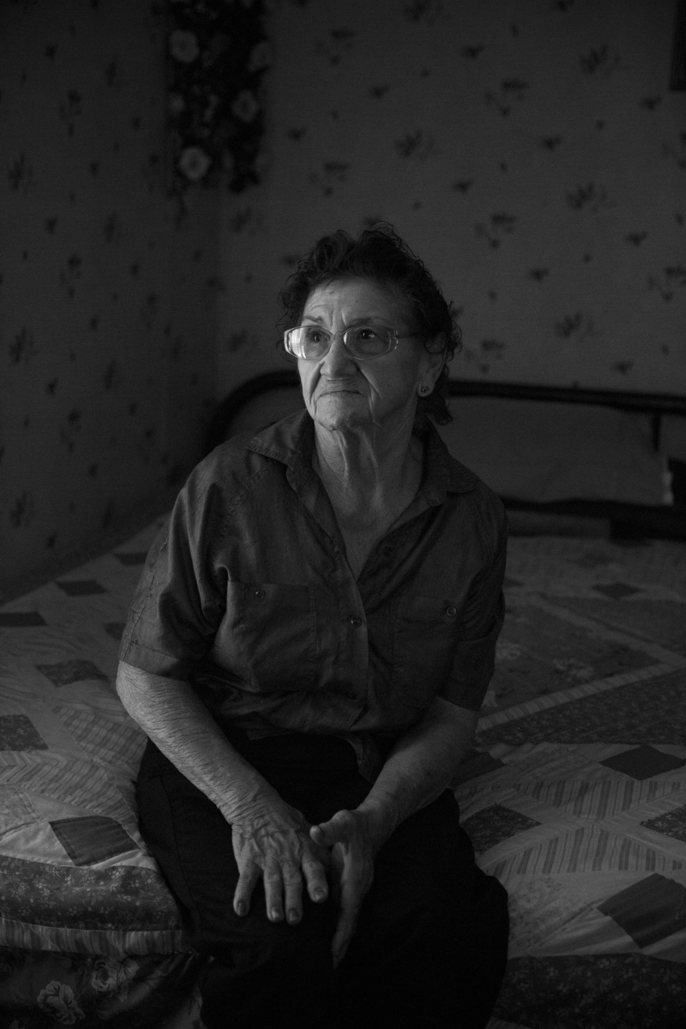 "Trine Tellez, who has two sons who worked in the oil field, sits for a portrait in her bedroom in Cotulla, Texas on June 19, 2015.  She said she worried when they would go to work.  ""Who would take care of me if something happened to you?"" she would ask. One of her sons, Ysmael ""Smiley"" Tellez who has since left the oil field, lives with her now and helps to take care of her."