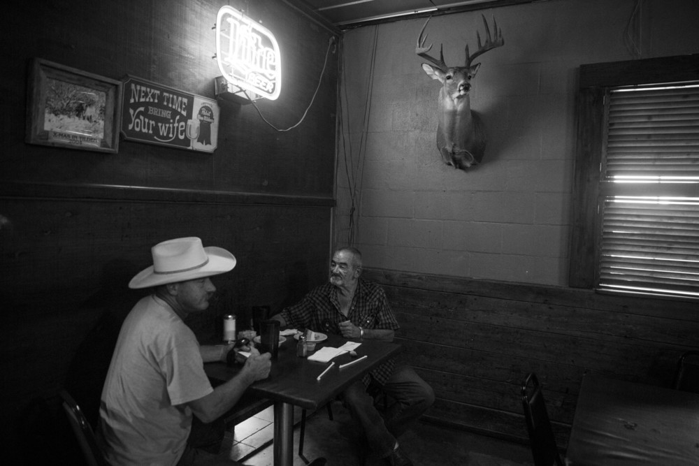 "Ronnie Moore and Billy Davis eat lunch at JJ's Country Store in Cotulla, Texas on August 5, 2015.  They both haul frac sand in the Eagle Ford Shale region.  ""Damn near overnight we started making half of what we used to make,"" Moore said. ""All you hear is talk.  Nobody knows what is going to happen.  I want to retire soon, but my wife doesn't want me home all the time."""