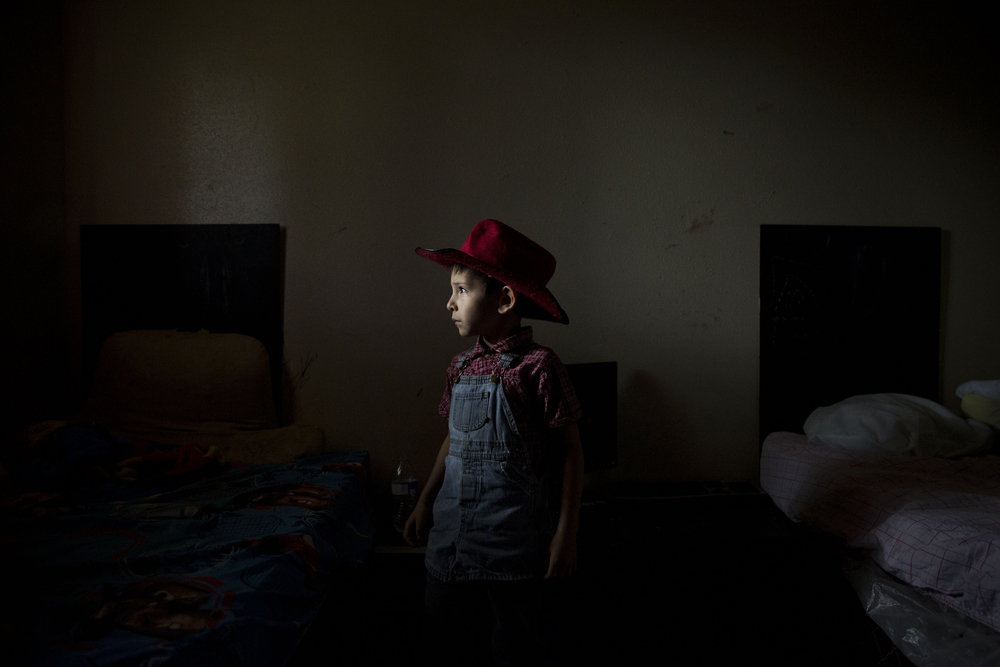Caiden Contreras, who has autism, stands for a portrait in the room he shares with three of his brothers at his home in San Antonio, Texas on May 27, 2015.  His parents are both unemployed and living off of his and some of his siblings' disability checks, as well as several other forms of financial assistance from the government.  His mother Sandra Contreras homeschools Caiden and four of his seven siblings at their home.