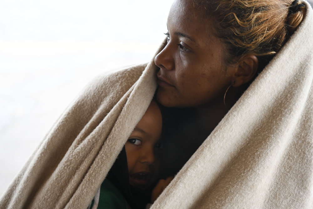 Cindy Romero, 24, from Honduras, holds her son Jason Velasquez, 2, and shields him from the cold winds coming off of the Pacific ocean as they wait with friends at the beach on November 29, 2018 in Tijuana, Mexico. They were weighing their options and deciding whether they should cross the border illegally at the beach to ask for asylum.