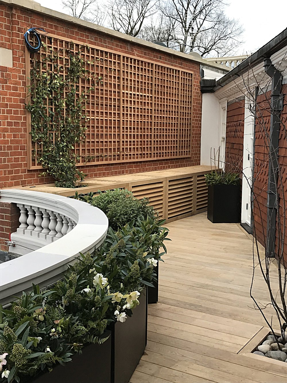 Designed by Butter Wakefield. Louvred AC unit covers, wall-mounted trellis and framed deck. Hampstead, London