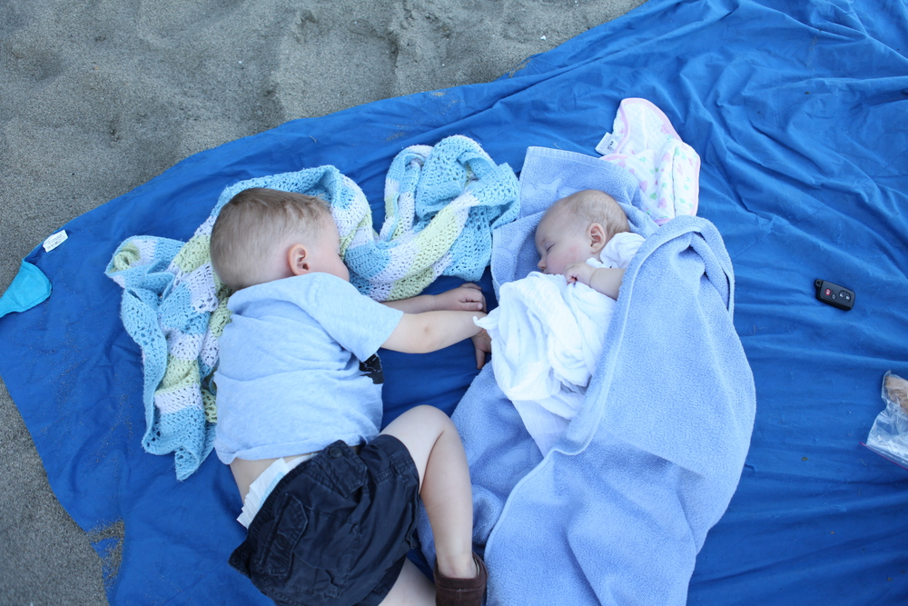 napping with his little sister on the beach.