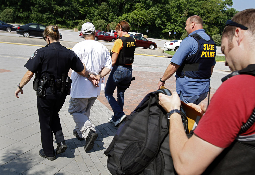 7/24/13 -- Newport News police officers Danielle Lawrence and Lisa Uzzle walk a man who was named in a warrant to a squad car at Phoebus High School. They are escorted by state police officer Henry Crawford, as Newport News police officer William Soule, right, looks over the contents of the man's backpack.
