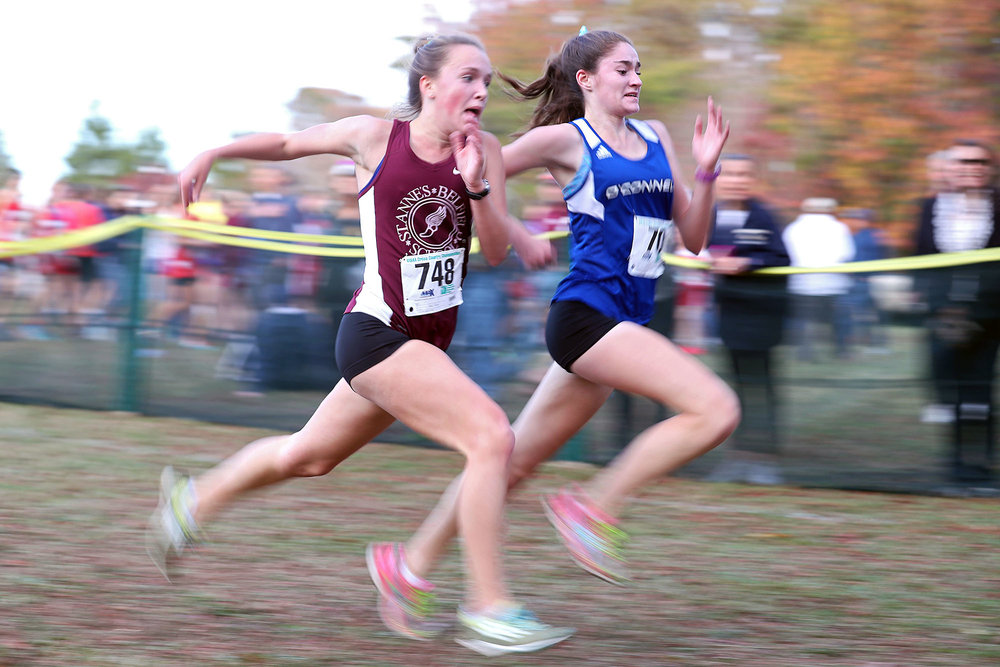 St. Anne's-Belfield's Clara Duffy (left) and Bishop O'Connell's Maeve Marsh race to the finish line during the VISAA state championship cross country meet at Fork Union Military Academy on Friday, Nov. 11, 2016.