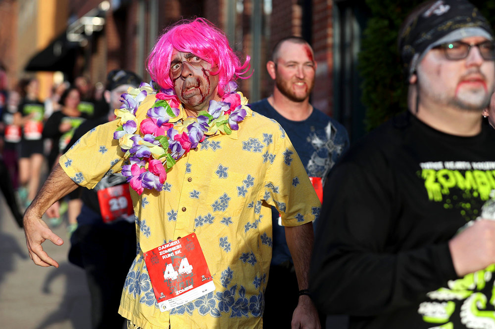 "Matt Hodges and other runners come down Water Street during the ""Danger! Zombies! Run!"" 5K on the Downtown Mall in Charlottesville on Sunday, Oct. 30, 2016. ""Human"" runners had a 90-second head start until ""zombie"" runners were released to chase them down along the course."