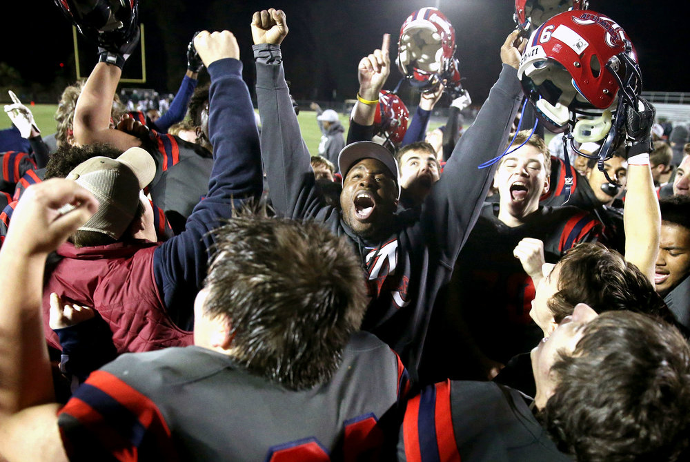 Albemarle head coach Brandon Isaiah celebrates after a first round VHSL 5A playoff football game at Albemarle High School on Friday, Nov. 11, 2016. Albemarle defeated Falls Church 31-21.