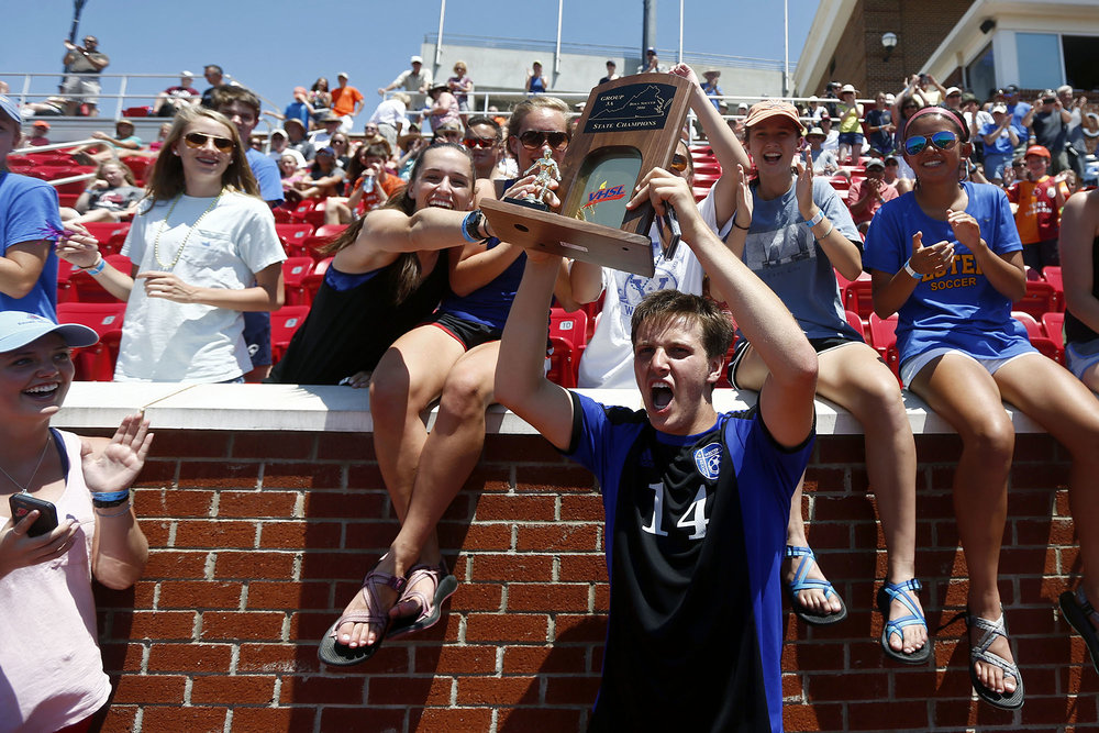 Western Albemarle's Jacob Paulson (14) hoists the trophy to celebrate with fans after winning the VHSL soccer championship in Lynchburg, Va. on Saturday, June 11, 2016.