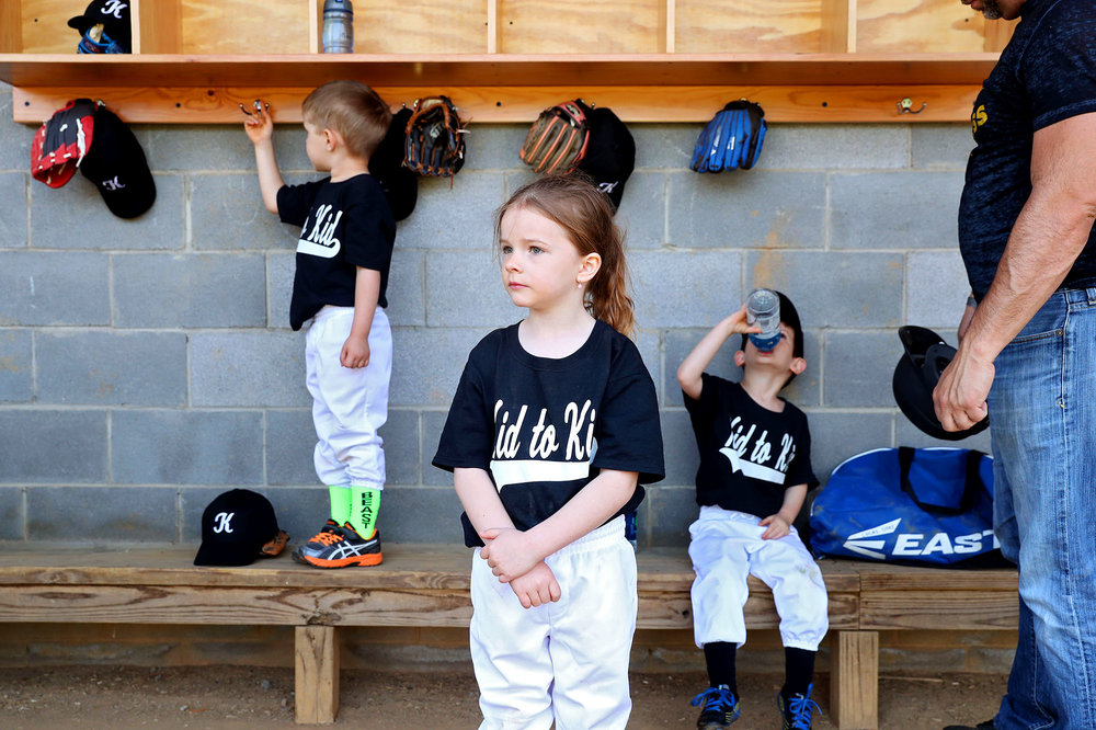 Stella Wolfe watches the game from the dugout as she waits for her turn to bat during the Central Little League opening day at Pen Park in Charlottesville, Virginia on Saturday, April 15, 2017.