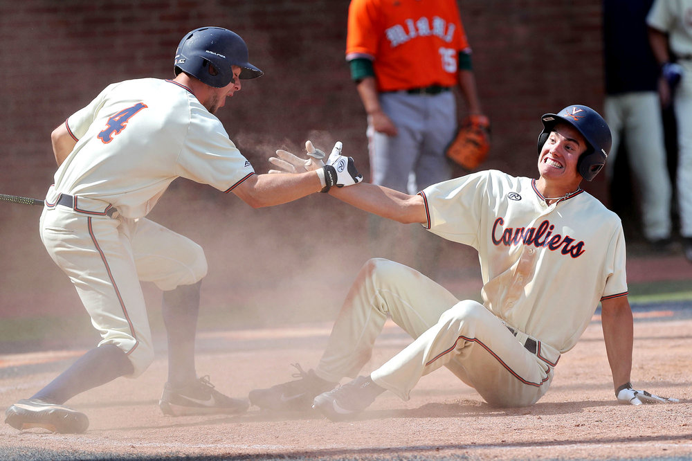 Virginia outfielder Cameron Simmons (20) slides safely into home to score a run and celebrates with Ernie Clement (4) during an NCAA college baseball game on Sunday, May 14, 2017. Virginia defeated Miami 7-4.