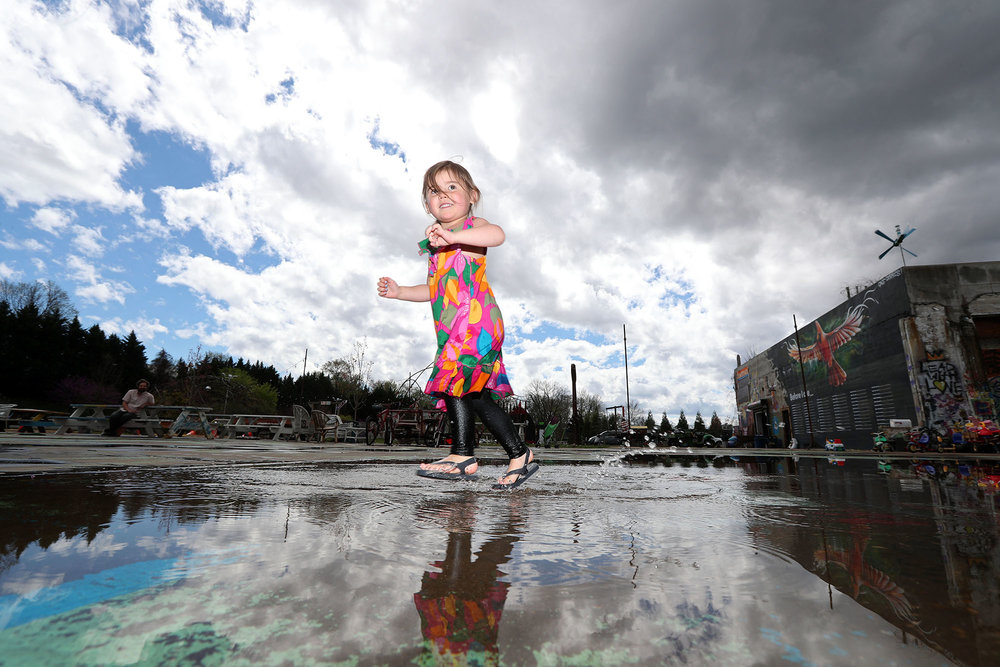 Katrina Schuler, 3, splashes in a puddle while she runs through the IX Art Park on Thursday, April 6, 2017. Early thunderstorms gave way to partly sunny skies throughout the day.