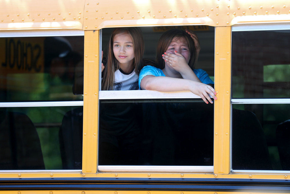 Daphne Waring (left) comforts Megan Marrs as their bus departs Yancey Elementary School after the last day of school on Friday, June 9, 2017. The Albemarle County School Board has voted to close the school, sending students to Red Hill and Scottsville elementary schools next year.
