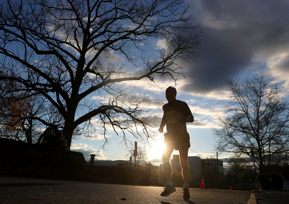 A runner passes Maplewood Cemetery as he runs up Maple Street during the Charlottesville Marathon, Half Marathon and 8K while the sun rises on Saturday, April 1, 2017.