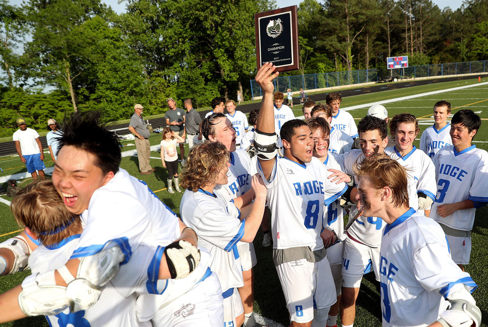 Blue Ridge defender Justin Armwood (8) hoists a plaque as teammates celebrate winning a boys lacrosse game against North Cross at Blue Ridge School on Wednesday, May 10, 2017. Blue Ridge defeated North Cross 16-8 to win the VIC championship.