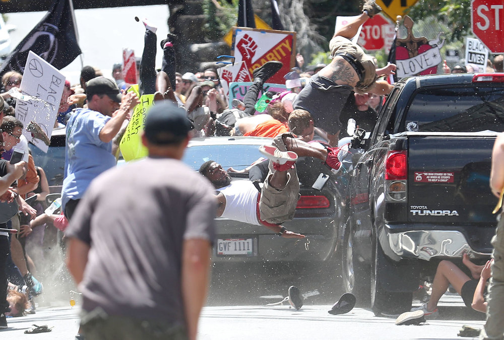People are thrown into the air as a car plows into a group of protesters demonstrating against the Unite the Right rally in Charlottesville, Virginia, on Aug. 12, 2017. The attack killed Heather Heyer and injured 19 others. James Alex Fields Jr., the alleged driver, was charged with second-degree murder. The white nationalist rally was originally organized to protest the city of Charlottesville's plans to remove a statue of Confederate Gen. Robert E. Lee.
