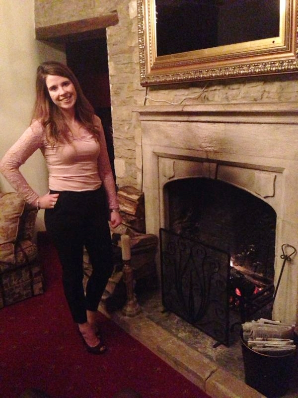 Birthday Gal pose by the fire, feeling decisively full, one happy girl.