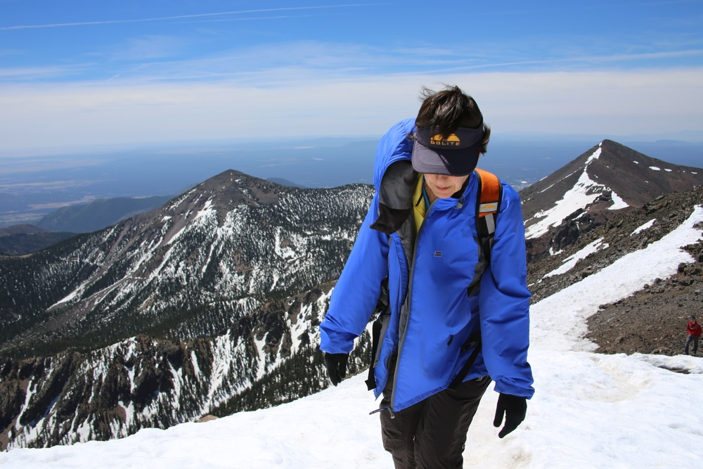Karen climbing a snowfield just below the summit.  Agassiz Peak, Arizona's second highest peak at 12,356 feet, can be seen to the right.