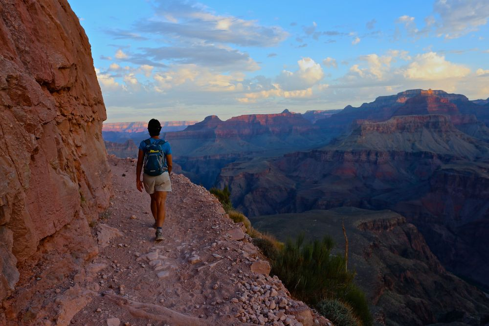 Karen traverses above the Tonto Plateau on the South Kaibab Trail as sunrise exposes the colors of the canyon.