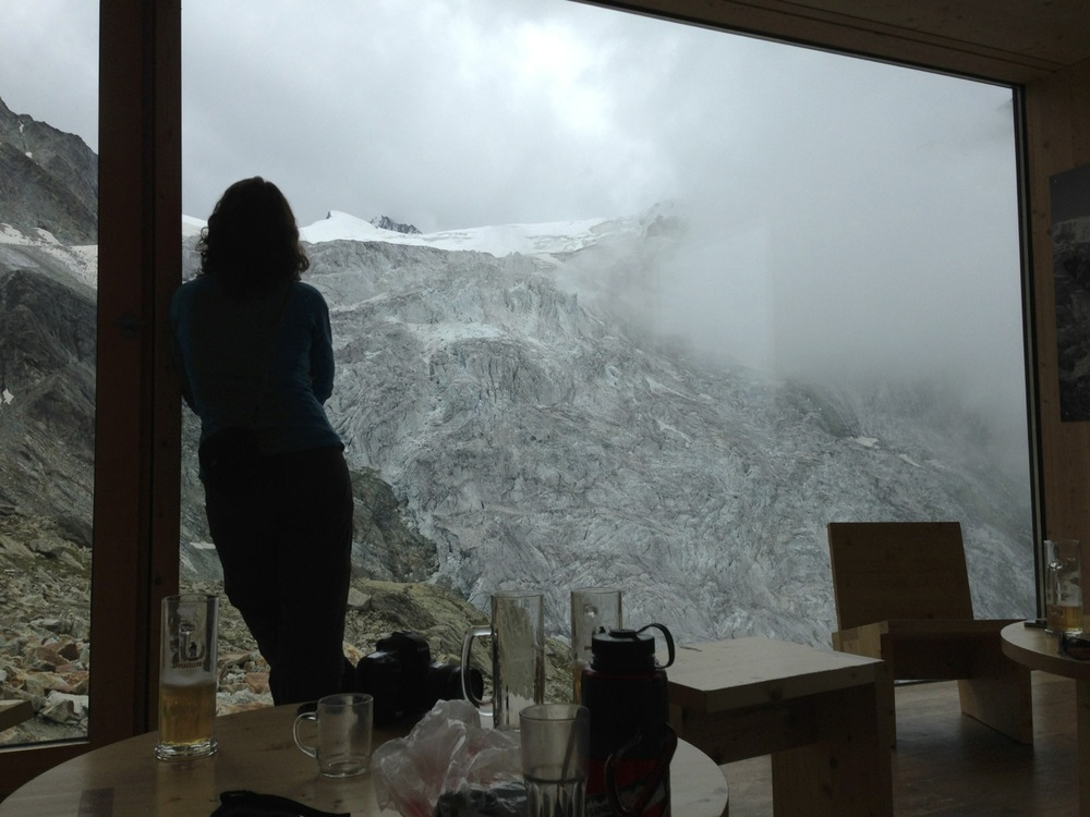 A fellow hiker looks out at the Moiry Icefall from the glass walled dining room of the Cabane de Moiry.