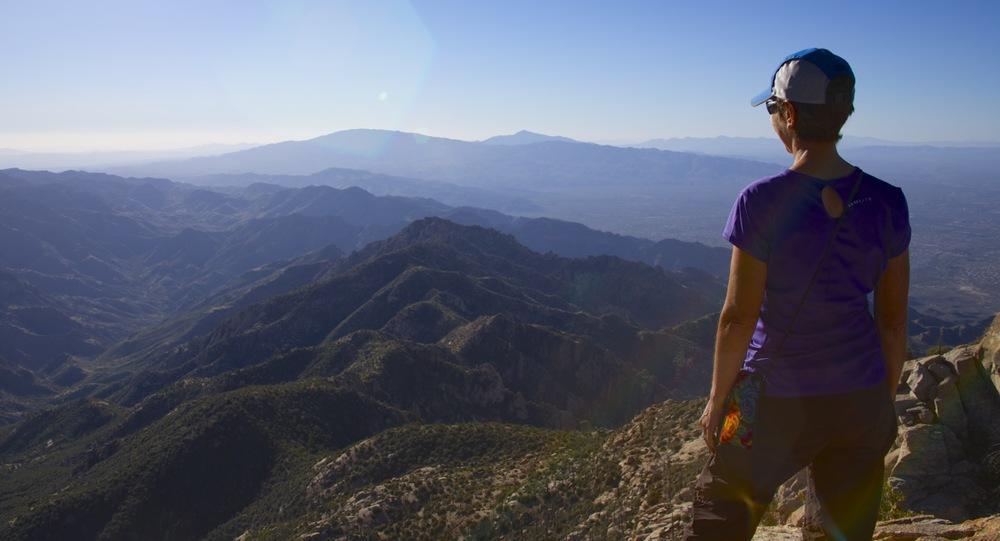 The view from the summit of Cathedral Rock is the best in the Santa Catalinas. Here, Karen looks southeast, with the drainage of the east and west forks of Sabino Creek on the left, and the Rincon Mountains of Saguaro National Park in the center distance (Mica Mountain on the left, and Rincon Peak on the right).