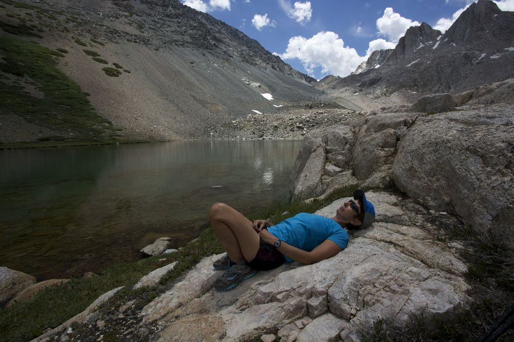 Karen rests at Sheperd Lake after the descent from Sky Pilot Col. The Col is the distant notch above Karen.