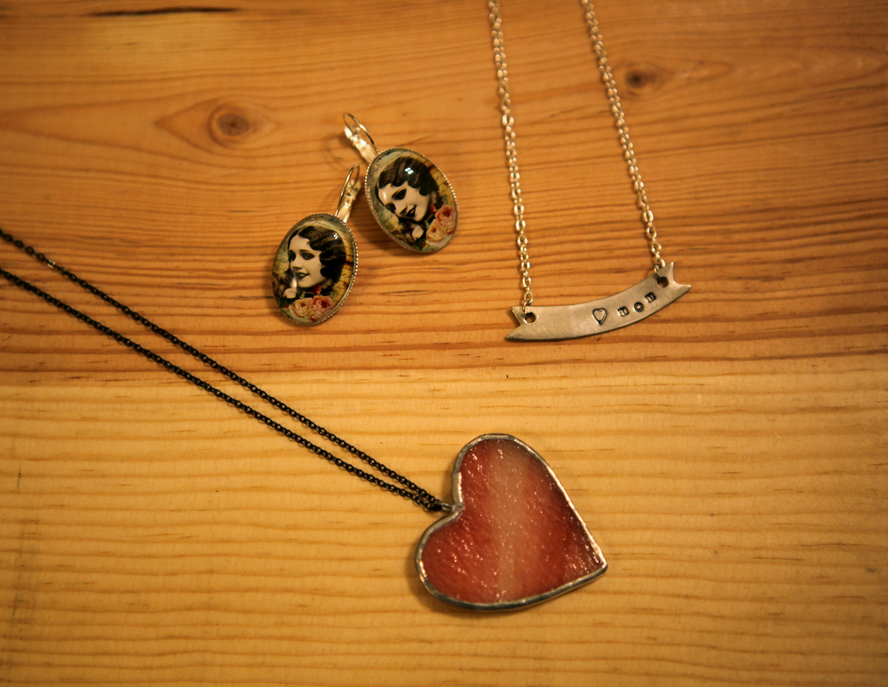 "Glass heart necklace made by Glass Action, $25.00.  Silver ""mom"" banner necklace by Dear Darlington, $24.00.  Lady oval earrings by Trollaphant, $15.00."