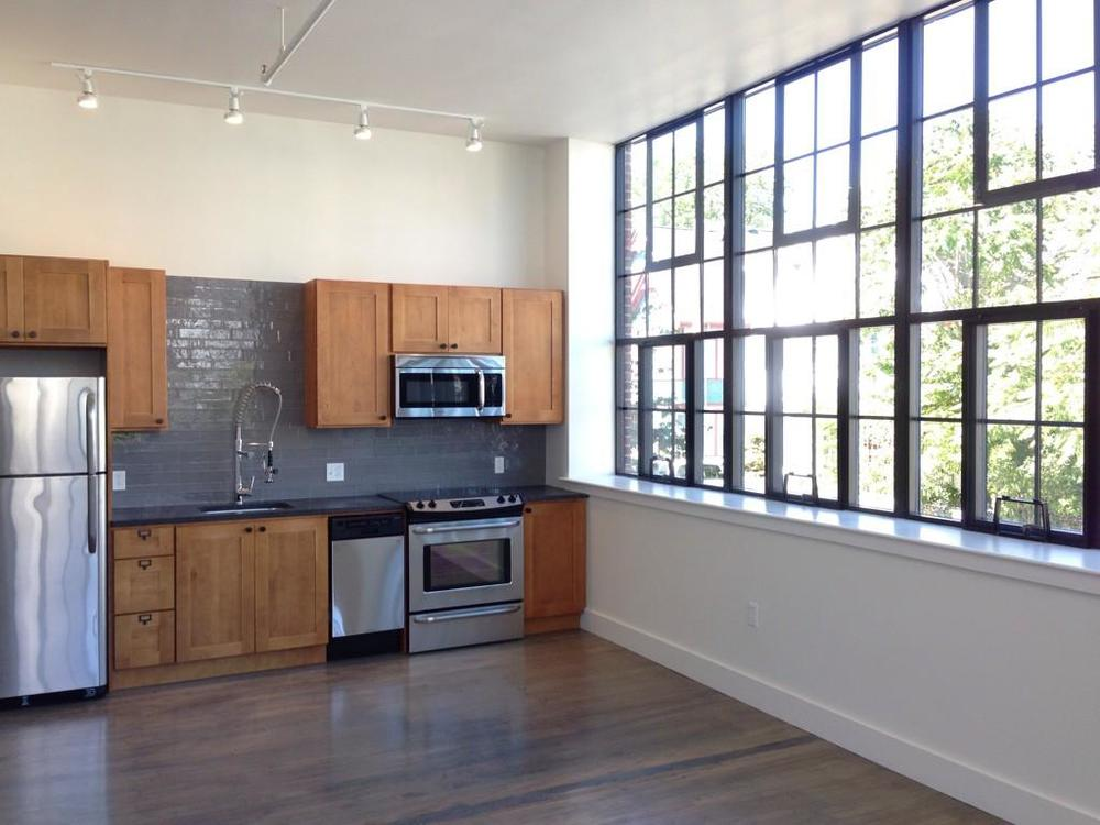 A second story loft space with original hardwood floors, full size windows, tall ceilings, and stainless appliances.