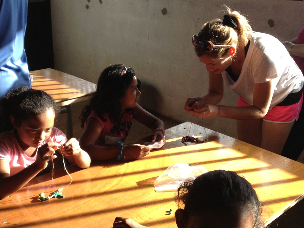 Lucinda Anne (Luci Butler) helps local children thread beads onto their new necklaces during a mission trip in El Mirador, Costa Rica.
