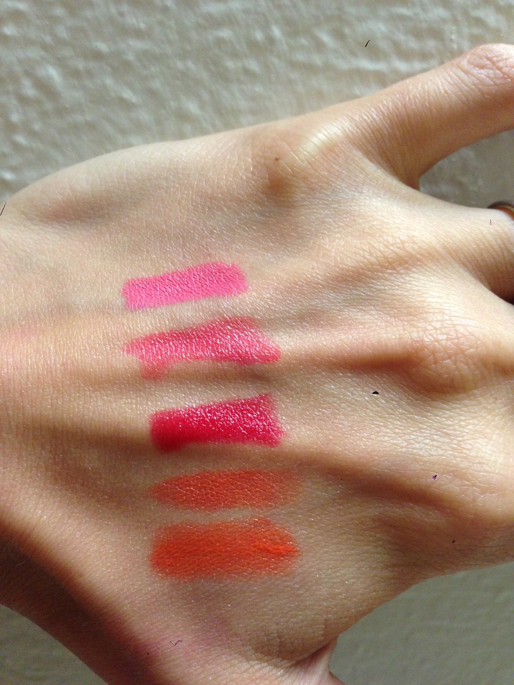 From top to bottom:  MAC satin VIVA GLAM NICKI, Maybelline COLORsensational in 870 Shocking Coral, Maybelline COLORsensational in 895 On Fire Red, Revlon Super Lustrous Lipstick in 677 Siren, Revlon Just Bitten Kissable Balm Stain in 040 Rendezvous