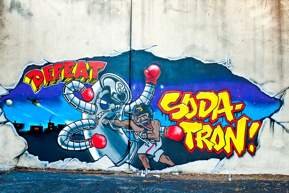 Operation: DEFEAT SODATRON - a youth led, art inspired revolution against BIGSODA's aggressive efforts to sell our communities a drink known to cause disease.