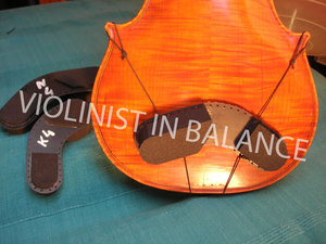 Boomerang Collar Bone Rest can be attached with elastics in any position on the instrument, using the range of holes provided along the edge. There is a space between the rest and the violin to ensure minimal interference with resonance.