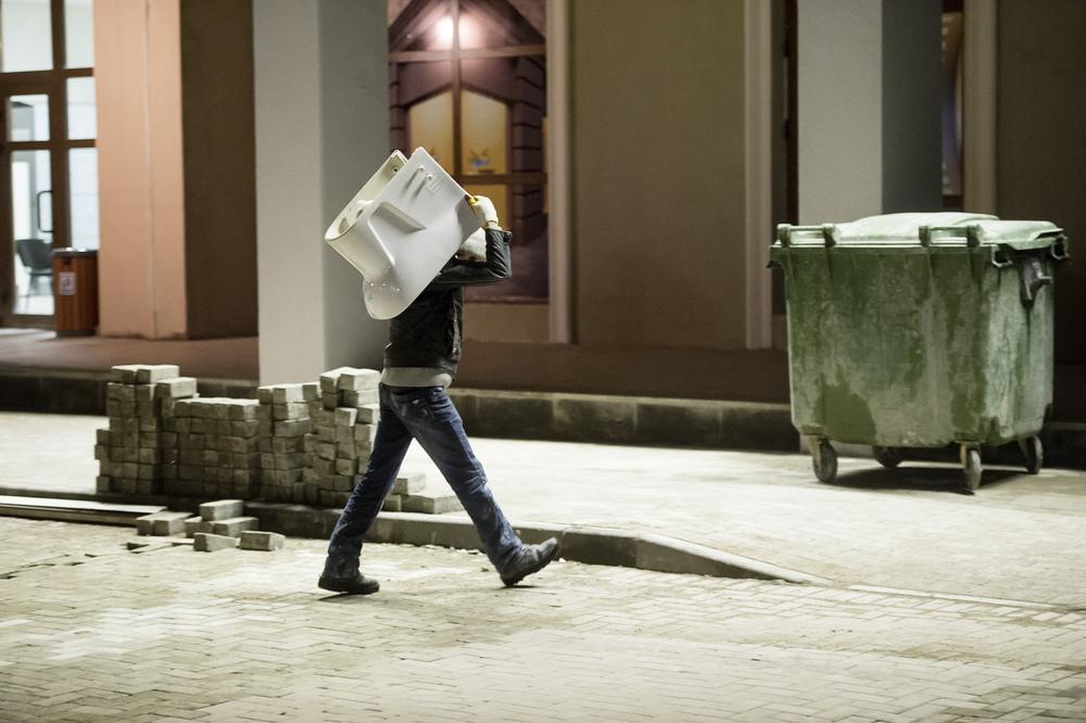 O2:08, en arbetar bär in en toalettstol i ett halvfärdigt hotell.